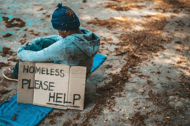 Les Mendiants Assis Dans La Rue Avec Des Messages Pour Les Sans-abri, Veuillez Aider. Photo gratuit