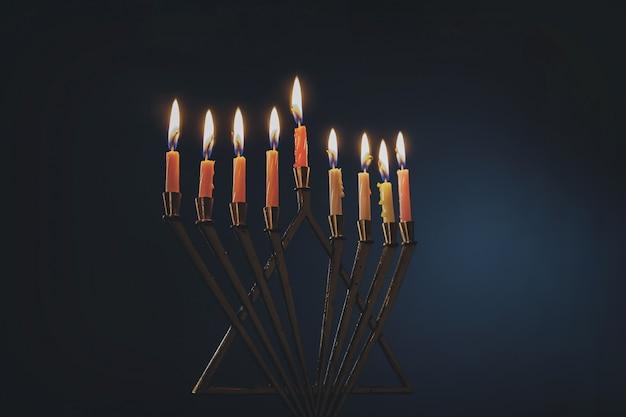 Menorah avec des bougies colorées pour hanoukka sur fond bleu clair, gros plan Photo Premium