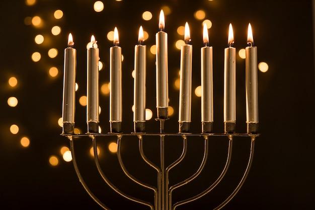 Menorah avec des bougies près de lumières abstraites guirlande Photo gratuit