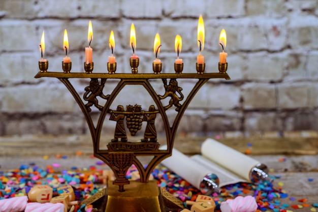 Ménorah en bronze à hanoukka avec bougies allumées sur le vieux millésime Photo Premium