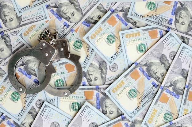 Les menottes argentées de la police reposent sur des billets de plusieurs dollars Photo Premium