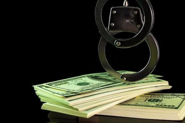 Les menottes ont été accrochées à un billet de banque en dollars dans le noir. Photo Premium