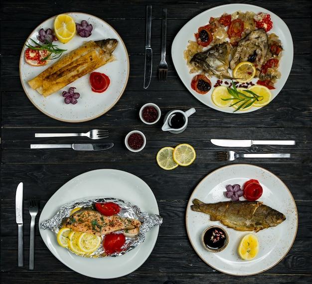 Menu du dîner pour 4 personnes, différents poissons, plats de fruits de mer dans des assiettes blanches avec couverts et sauces Photo gratuit