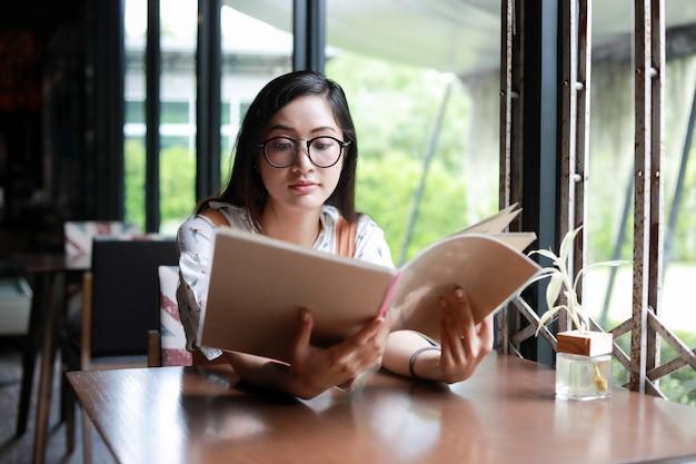 Menu ouvert femme asiatique pour commander dans un café café et restaurant et souriant pour un temps heureux Photo Premium