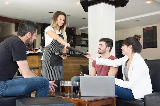 Menu de présentation de serveuse à une cliente avec des amis au bar Photo gratuit