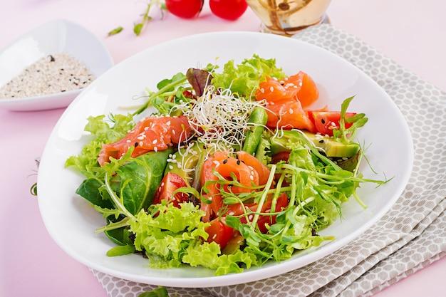 Menu de régime. salade saine de légumes frais - tomates, avocat, roquette, graines et saumon Photo Premium