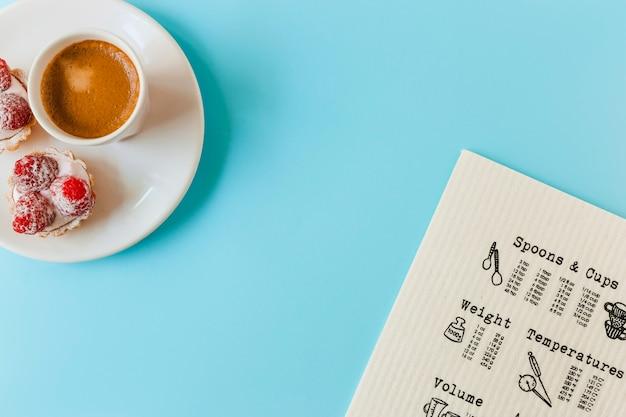 Menu; tarte aux fruits maison et tasse de café sur la plaque sur le fond bleu Photo gratuit