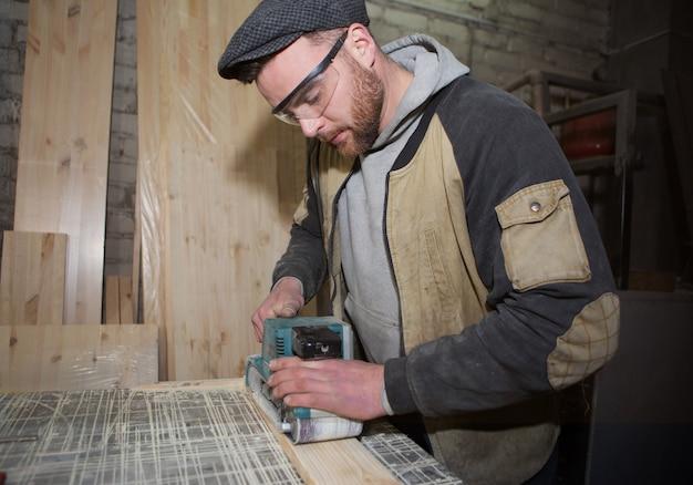 Menuisier Travaillant Avec Une Ponceuse électrique Manuelle Sur Le Bureau En Production Photo Premium
