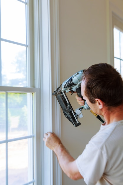 Menuisier utilisant un pistolet à clous pour mouler des fenêtres, encadrer des moulures, Photo Premium