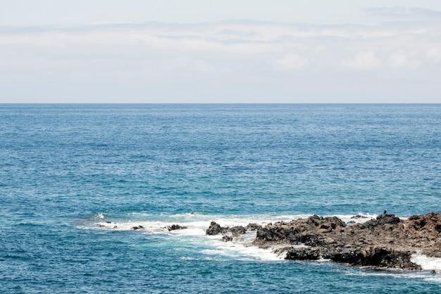 Mer bleue avec littoral rocheux Photo gratuit