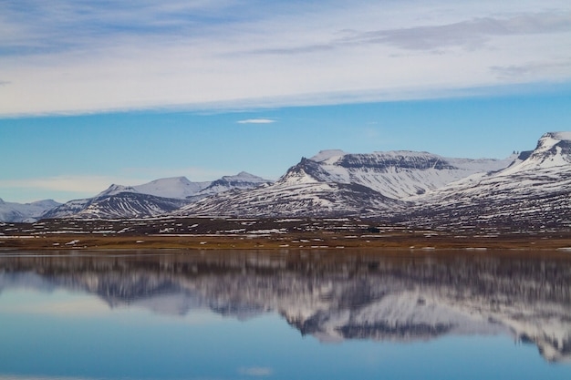 Mer Entourée De Montagnes Rocheuses Couvertes De Neige Et Se Reflétant Sur L'eau En Islande Photo gratuit