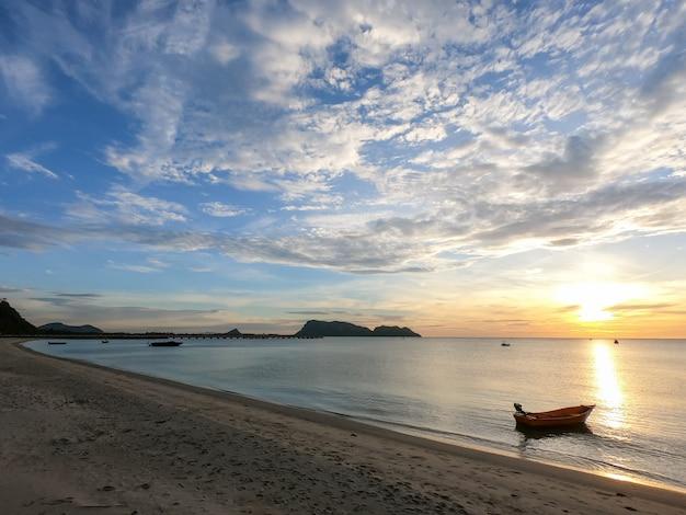 Mer en saison estivale au lever du soleil avec petit bateau et ciel nuageux. Photo Premium