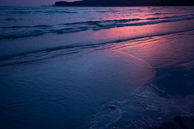 Mer sombre plage de sable fin et soleil rouge coucher de soleil crépuscule Photo Premium