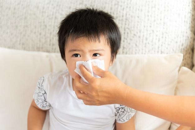 Mère aidant sa fille à se moucher à la maison dans le salon. Photo Premium