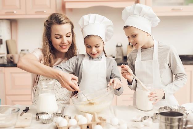 La Mère Aide Les Enfants à Mélanger Des Ingrédients Pour La Pâte. Photo Premium