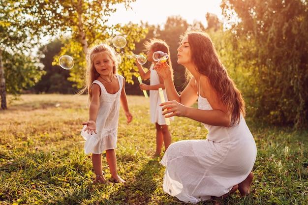 Une Mère Aide Ses Filles à Souffler Des Bulles Dans Un Parc D'été Photo Premium