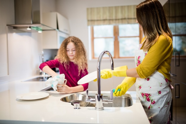 Mère d'aider sa fille dans la plaque de lavage dans la cuisine Photo gratuit