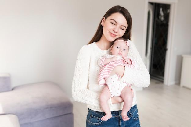Mère aimante avec bébé sur les mains Photo gratuit