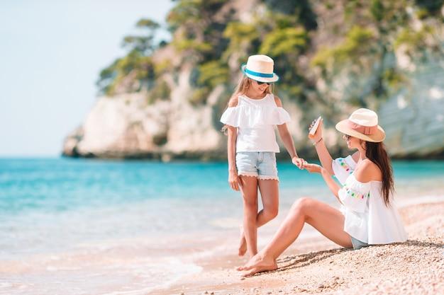 Mère appliquant une crème de protection solaire à sa fille sur une plage tropicale Photo Premium