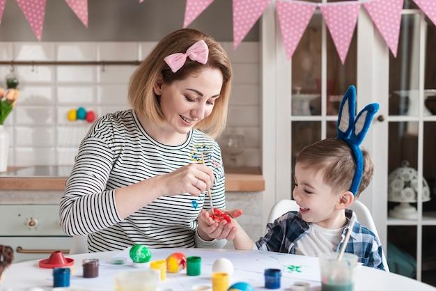 Mère Apprenant à Son Fils à Peindre Des œufs Pour Pâques Photo gratuit