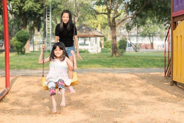 Mère asiatique balançant balançoire pour sa fille, jolie fille est tellement amusant et bonheur dans l'aire de jeux, temps de la famille heureuse Photo Premium