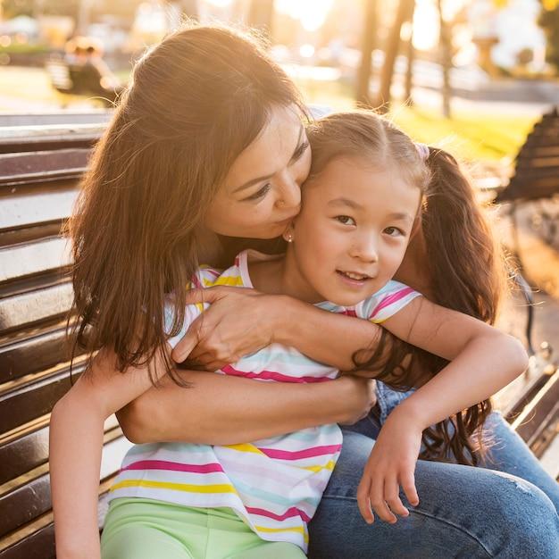 Mère Asiatique Embrassant Son Enfant Sur La Joue Photo Premium