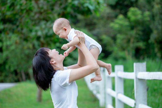 Mère asiatique portant son petit garçon. sourire et s'amuser ensemble. Photo Premium