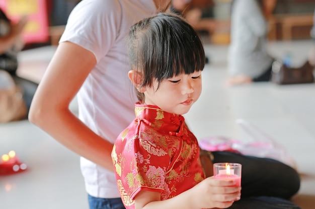Une mère asiatique et sa fille en costume traditionnel allument les bougies du culte au temple chinois Photo Premium