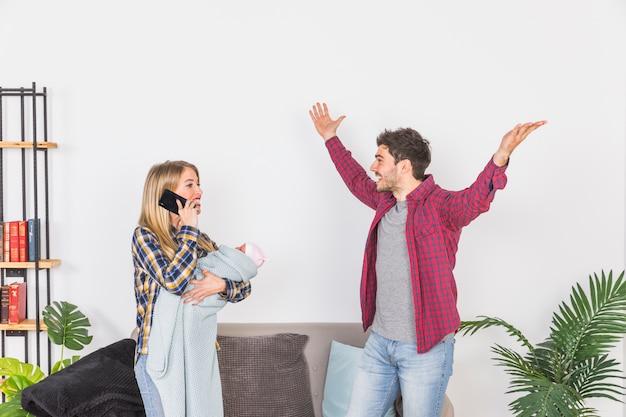 Mère avec bébé parle au téléphone près de père heureux Photo gratuit