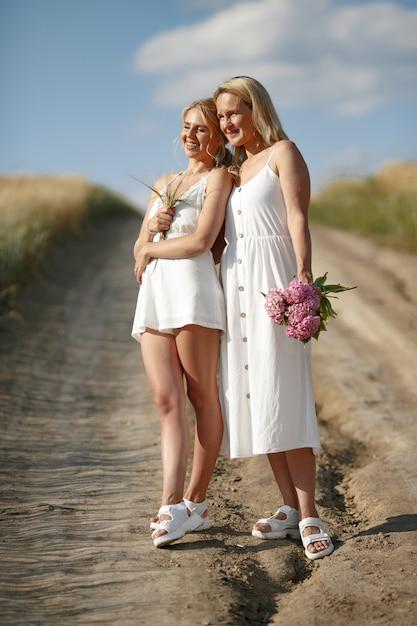 Mère avec belle fille dans un champ d'automne Photo gratuit