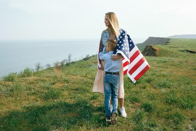 Mère Célibataire Avec Fils Le Jour De L'indépendance Des états-unis. Femme Et Son Enfant Marchent Avec Le Drapeau Américain Sur La Côte De L'océan Photo Premium