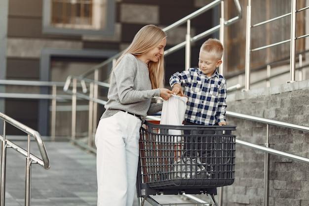 Mère Conduit Dans Un Chariot. Famille Dans Un Parking Près D'un Supermarché. Photo gratuit