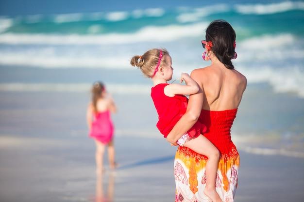 Mère et deux adorables filles marchant sur une plage exotique par une journée ensoleillée Photo Premium