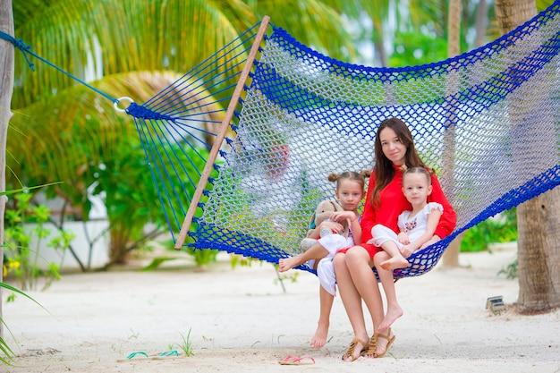 Mère et deux enfants assis sur un hamac sur une plage tropicale Photo Premium