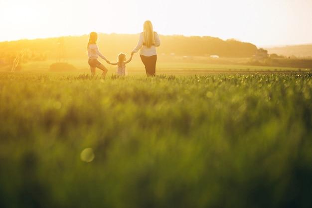 Mère avec deux filles au coucher du soleil Photo gratuit