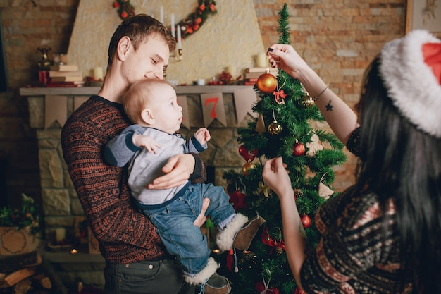 Mère Distraire Le Bébé Avec Un Ornement De Noël Tandis Que Le Père Tient Dans Ses Bras Photo gratuit