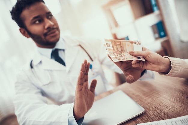 La mère donne de l'argent au docteur. le docteur refuse. Photo Premium