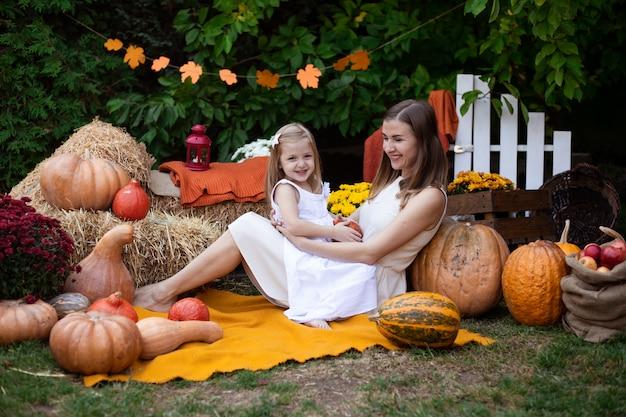 Mère embrassant sa fille en automne fond avec des citrouilles Photo Premium