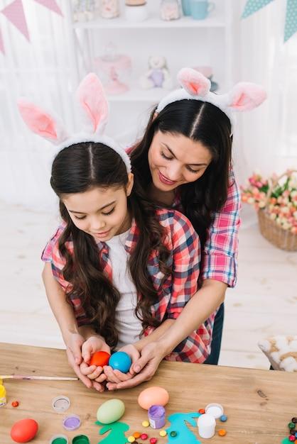 Mère embrassant sa fille tenant des oeufs rouges et bleus le jour de pâques Photo gratuit