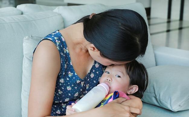 Mère embrasse sa fille enfant buvant à une bouteille sur le canapé Photo Premium