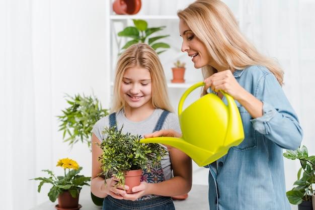 Mère Et Enfant Arrosant Des Fleurs Photo gratuit