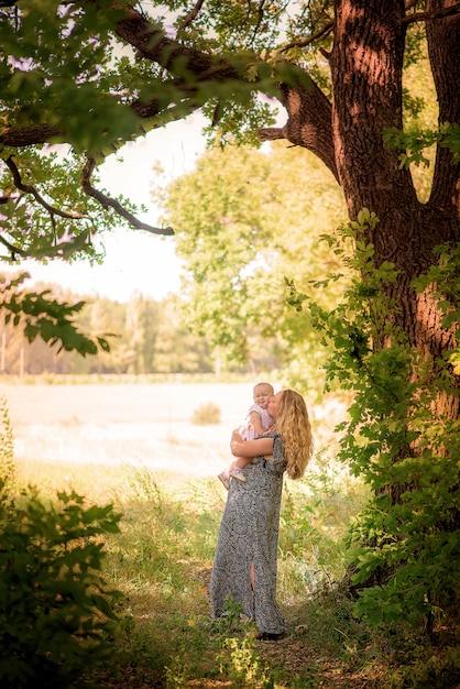 Mère et enfant dans la forêt d'automne jouent Photo Premium