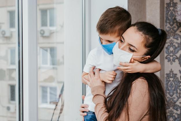 Mère Avec Un Enfant Dans Des Masques Médicaux Est Assise à La Maison En Quarantaine Et Regarde Par La Fenêtre. Prévention Des Coronovirus Et Covid -19 Photo Premium