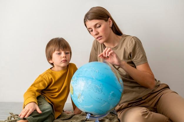 Mère Et Enfant Avec Globe à La Maison Photo gratuit