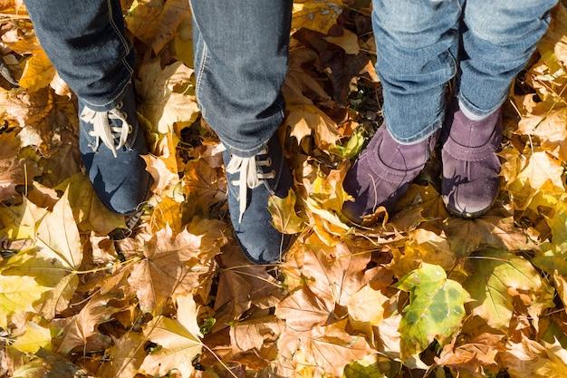 Mère et enfant pieds d'en haut sur les feuilles d'automne Photo Premium
