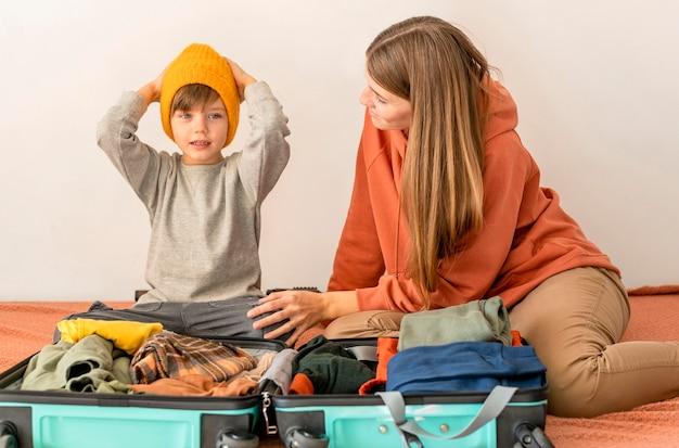 Mère Et Enfant Préparant Les Bagages Pour Voyager Photo gratuit