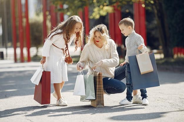 Mère avec enfant avec sac à provisions dans une ville Photo gratuit