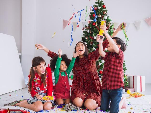 Mère et enfants célèbrent noël et s'amusent et sont heureux à la maison avec un sapin de noël Photo Premium