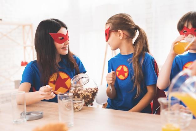 Mère avec enfants en costume rouge et bleu de super-héros. Photo Premium