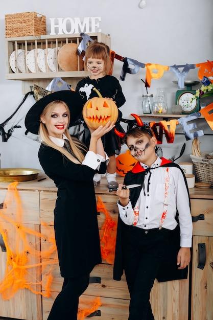Mère, enfants, cuisine, debout, déguisement, regarder appareil-photo, halloween Photo Premium